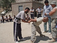 An police trainee handcuffs Petty Officer 2nd Class Jovener R. Mironchik while Seaman Brian L. Boyd Jr. watches during a training session with Afghan national auxiliary police students at a training facility near Asadabad