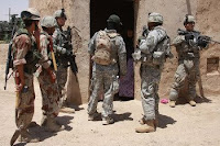 U.S. and Iraqi soldiers speak with a Baghdad resident about suspicious activity in the area. Cooperation between Coaliton and Iraqi security forces has resulted in an increasingly positive security situation, according to Ryan Crocker, U.S. Ambassador to Iraq