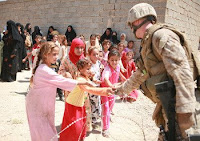 Lance Cpl. Gary A. Jacobs hands candy to little girls who wait with their mothers to be seen by a doctor during a Cooperative Medical Engagement in Fallujah, June 24.