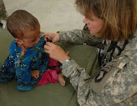 Navy Cmdr. Beth Myhre checks a girl's burn scars during a medical outreach in Nilay Village in the Kohe Sofe District, Parwan province, Afghanistan, June 26.
