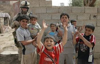 Iraqi children pose with Marine 1st Sgt. Robert W. Breeden during a patrol through Ramadi, Iraq. The patrols, performed with Iraqi Police, maintain security and assess the condition of the area.