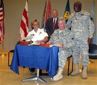 Cathy Lanier (seated, left), chief of the Metropolitan Police of the District of Columbia, and Army Maj. Gen. Peter Cook from the Army Reserve sign a partnership agreement to collaborate on recruiting during a July 14, 2008, ceremony. Looking on, left, are Assistant Secretary of Defense for Reserve Affairs Thomas Hall and Command Sgt. Maj. Leon Caffie, the top Army Reserve noncommissioned officer. Defense Dept. photo by Donna Miles