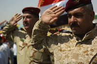 Members of the Iraqi army salute while the Iraqi national anthem plays during the Najaf International Airport inauguration ceremony, July 20.