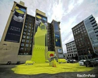 Outdoor enorme com propaganda derruba tinta pela fachada do prédio, sobre o pátio eos carros.