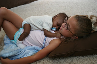 Young sister with her infant baby brother sleeping on her chest