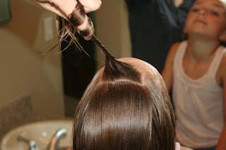 """Back view of young girl's hair being styled into """"Knots into Side Ponytail"""" hairstyle"""