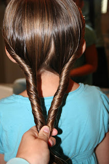 "Back view of a young girl having her hair styled into ""Double-twist"" ponytail"