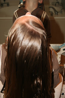 "Back view of girl's hair being styled into ""Zig-Zag Part"""