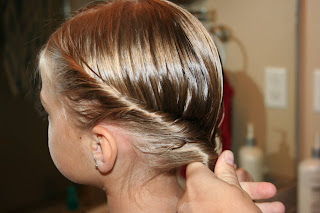 "Side view of a young girl having her hair styled into ""Double-twist"" ponytail"