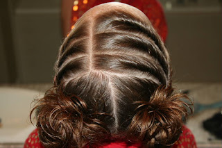 "Top view of young girl's hair styled into ""Triple Twists and Messy Buns"""