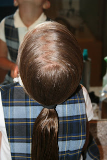 "Young girl's hair being styled in to ""Ponytail Of Twists"" hairstyle"