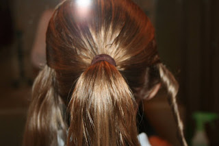 """Back view of young girl's hair being styled into """"Hair Headband"""" hairstyle"""