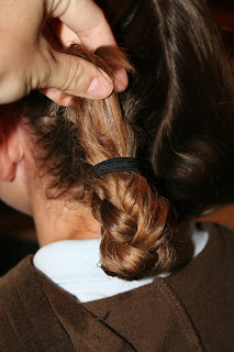 """Back view of young girl's hair being styled into """"Double-French Braids w/Messy Flips"""""""