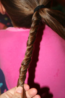 "Back view of young girl's hair being styled into ""Triple-Twist Ponytail' hairstyle"