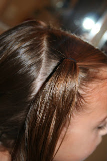 """Side view of young girl's hair being styled into """"4 Messy-Pigtail Twists"""" hairstyle"""