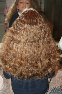 """Back view of young girl's hair being styled into """"Curls After Triple Twists w/ Messy Buns"""" hairstyle"""