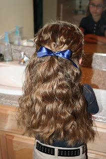"""Back view of young girl modeling """"Curls After Triple Twists w/ Messy Buns"""" hairstyle"""