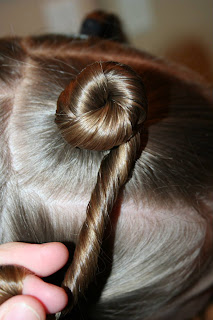 "Side view of young girl's hair being styled into ""Holiday Twisty Buns"" hairstyle"
