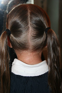 "Back view of young girl's hair being styled into ""Y"" braid hairstyle"