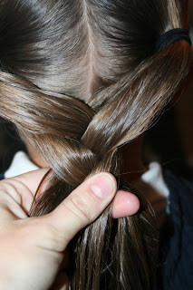 "Close up view of young girl's hair being styled into ""Y"" braid hairstyle"