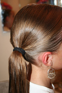 "Side view of young girl's hair being styled into ""Teen Hair Bun"" hairstyle"