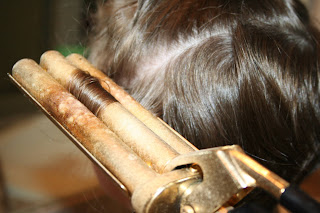 close up view of young girl's hair being styled into 3-barrel curl hairstyle on her a-line bob