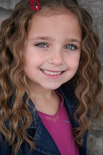 Portrait of young girl modeling 3-barrel curl hairstyle