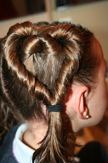 """Side view of a young girl's hair being styled into """"Two Hearts Twist"""" hairstyle"""