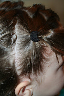 "Side view of a young girl's hair being styled into ""Heart Pigtail"" hairstyle"