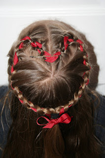 """Top view of a young girl modeling """"French Designer Heart"""" hairstyle with ribbon in her hair"""