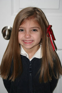 "Portrait view of young girl modeling ""teen heart"" hairstyle 3 styled with a red ribbon"