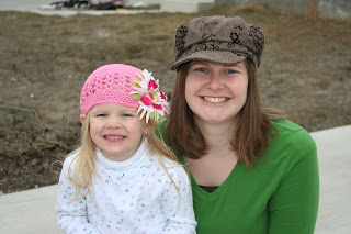 Portrait of young girl and her mother modeling giveaway prizes of hats