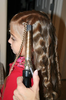 "Side view of young girl's hair being styled into ""Beachy Combo"" hairstyle"