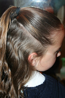 "Side view of young girl's hair being styled into ""Best Three-Leaf Clover"" hairstyle"