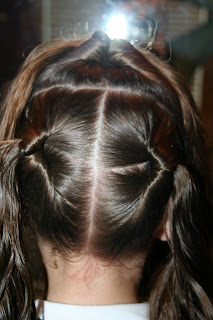 "Back view of young girl's hair being styled into ""Best Three-Leaf Clover"" hairstyle"