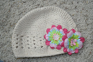 Product photo of cream beanie hat and two multi-color flower clips