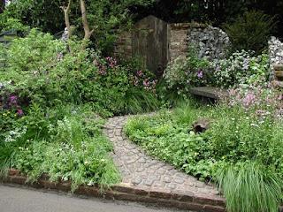 plante ornamentale in gradina, vegetatie luxurianta, gradina romantica, piatra cubica, poarta, idei