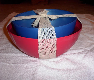 Large bowl with water in. A smaller bowl pushed into water and secured with bandage