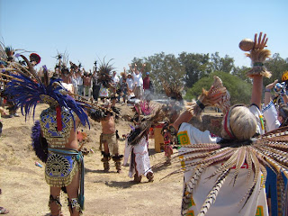 Grupo de danzantes durante el mediodía. Al fondo, visitantes con las manos levantadas recibiendo energía.