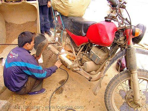 Moto sendo reparada na oficina por soldadaor
