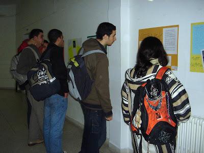 Alumnos contemplando con atención los carteles