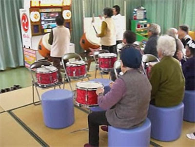 Namco Rehabilitainment Glimpses - Image of a group of elderly Japanese people playing drums alongside a Taiko Drummer video game
