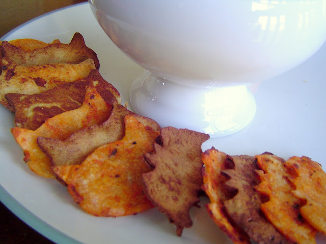 final photo of bat and cat shaped homemade tortilla chips lined up on a platter with a bowl to serve salsa in