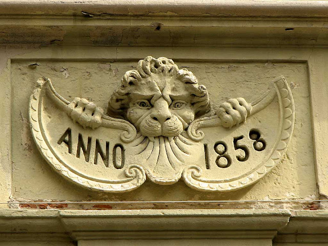 Mascaron with lion biting a scroll, via Roma, Livorno