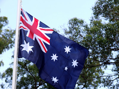 australian flag - photo of an australian flag waving in the breeze on a flag pole