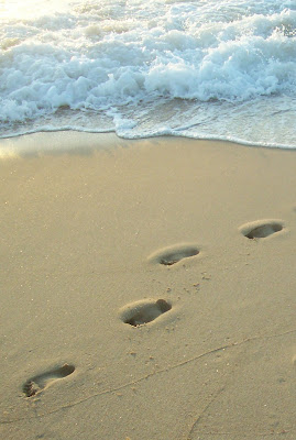 footprints in sand leading away from wave breaking on shore
