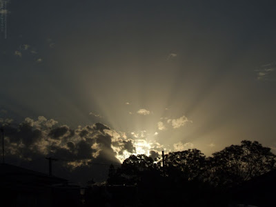 sunset with sun rays shining over urban rooftops with clouds - landscape photo of the sun setting