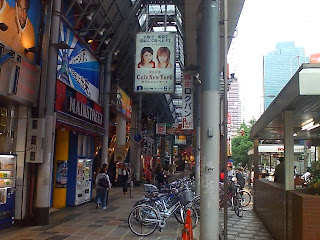 Anuncio por todo lo grande de un club de alterne en lo alto de una de las calles comerciales más transitadas mientras un niño pasa por debajo.