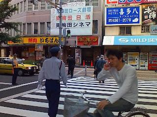 Como veis, esta es una zona por la que pasa gente de todos los tipos. Al lado del semáforo un hombre con una pancarta que anuncia un videoclub porno.