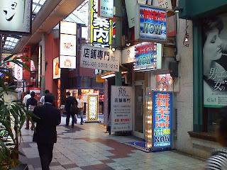 Tanto el cartel azul, en primer plano, como el cartel amarillo, detrás, son de Muryou Annaisho. A su lado, un restaurante y un karaoke al fondo con un letrero que lee ジャンカラ.